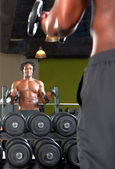 Mirror reflection of two men exercising in gym — Stock Photo