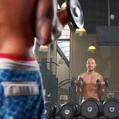 Reflexo do espelho de dois homens exercício no ginásio — Foto Stock