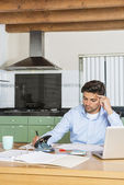 Young man sits at the kitchen table — Stock Photo