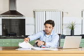 Young man sits at the table — Stock Photo