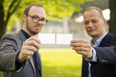 Businessmen presenting business cards — Stock Photo