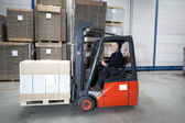 Forklift driving through warehouse — Stock Photo