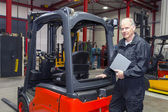 Forklift mechanic with manual — Stock Photo