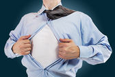 Young business man tearing apart his shirt revealing a superhero suit — Stockfoto