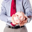 Business man holding a pig bank - economy savings — Foto de Stock