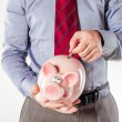 Stockfoto: Business man holding a pig bank - economy savings