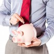 Foto de Stock  : Business man holding a pig bank - economy savings