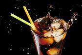 Chapoteo de cubos de cola fresca jugo y el hielo en un vaso sobre fondo negro — Foto de Stock