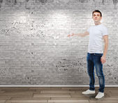 Portrait of casual young attractive man standing in front of a vintage wall — Stock Photo