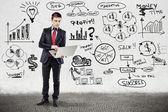 Homme d'affaires en costume et business plan sur mur de grunge — Photo