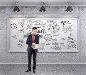 Grunge 墙上的西装和业务计划的商人 — 图库照片