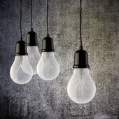 3d light bulb on vintage concrete wall — Stockfoto