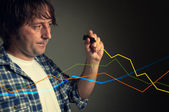 Casual man drawing a rising chart — Stock Photo