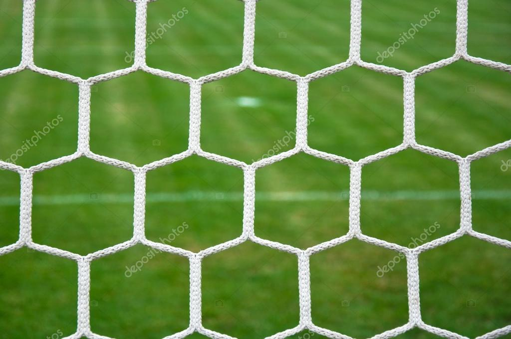 Close up detail of a soccer net against green grass — Stock Photo #13439761