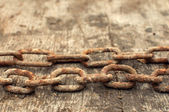 Rusty chain and weathered wood background — Stock Photo