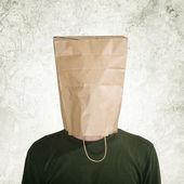 Verborgen achter een papieren zak — Stockfoto