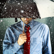 Businessman with umbrella in storm - Stock Photo