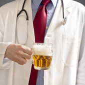 Doctor is drinking beer — Stock Photo