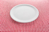 Empty plate on kitchen table — Stock Photo