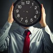 Businessman with black clock, deadline concept - Stock Photo