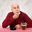 Stock Photo: Beer drinker lighting up cigarette