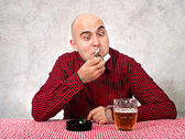 Beer drinker lighting up a cigarette — Stock Photo