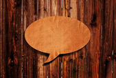 Speech balloon on wood background — Stock Photo
