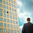 Stock Photo: Businessman in front of company building.