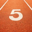 Number five on running track - Stock Photo