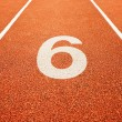 Number six on running track - Stock Photo