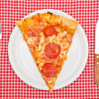 Pepperoni pizza slice on white plate — Stock Photo