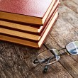 Books and reading glasses on table — Stock Photo
