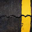 Yellow line on cracked asphalt road — Stock Photo
