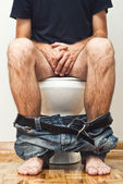 Man sitting on toilet — Stock Photo