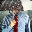 Businessman with umbrella in storm — Stock Photo
