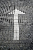 White arrow on pavement — Stock Photo