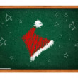 Santa Claus hat on green chalkboard — Stock Photo