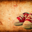 Baby sneakers on grunge paper — Stock Photo