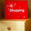 Red Christmas Shopping bag on wooden drawer — Stock Photo #37139589