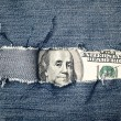 Hundred dollars bill through torn blue jeans texture — Stock Photo