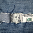 Hundred dollars bill through torn blue jeans texture — Stock Photo #37623617