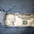 Twenty dollars bill through torn blue jeans texture — Stock Photo #37625063