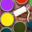 Stock Photo: Paint roller and color tin cans of color on wooden background