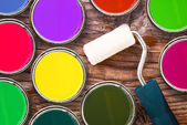Paint roller and color tin cans of color on wooden background — Stock Photo