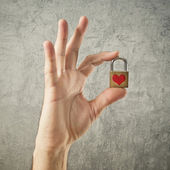 Hand holding padlock with heart shape — Stock Photo