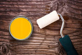 Paint roller and color tin can on wooden background — Stock Photo