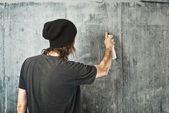 Graffiti artist spraying the wall — Stock Photo