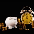 Golden coin stack, piggy coin bank and vintage clock on dark bac — Stock Photo