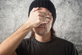 Casual Man with Black Cap covering face — Stock Photo