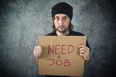 Man holding cardboard paper with Need a Job message — Stock Photo